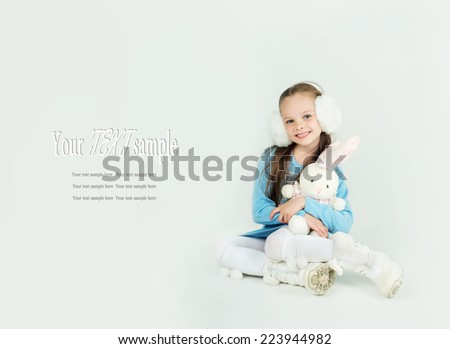 Cute girl in winter clothes with a white blank paper sheet. Winter, Christmas, x-mas, New Year, people, advertisement, sale concept. Facial expressions. - stock photo