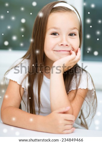 Cute girl is daydreaming while sitting at table, over snowy background - stock photo