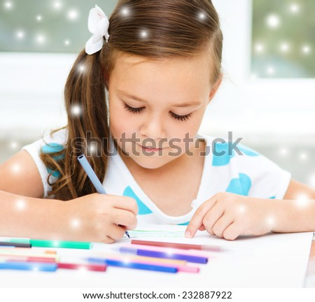 Cute girl is drawing using color pencils, over snowy background - stock photo
