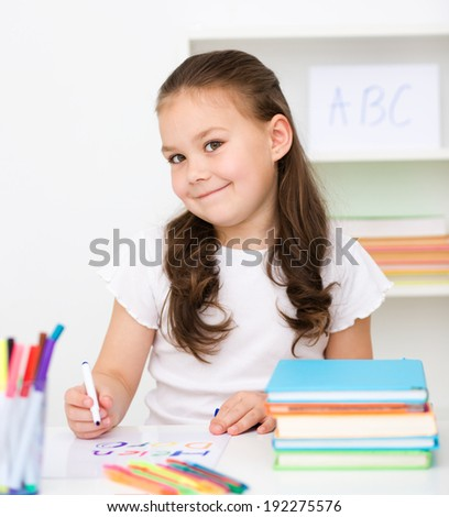 Cute girl is drawing using color pencils while sitting at table - stock photo