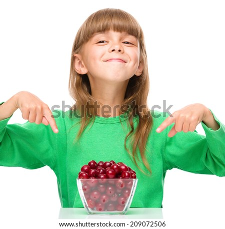 Cute girl is eating cherries and pointing to them using index fingers, isolated over white - stock photo