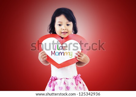 Cute girl is holding a valentine card with the word I - stock photo