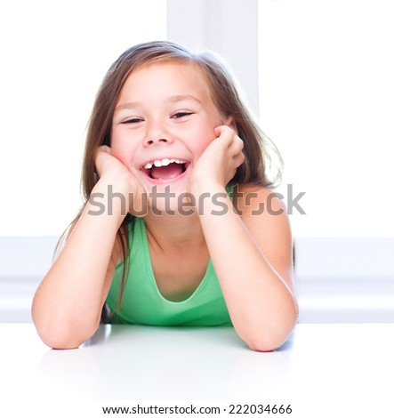 Cute girl is holding her face in astonishment and looking up - stock photo