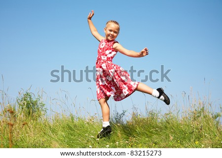Cute girl jumping on summer meadow against blue sky - stock photo