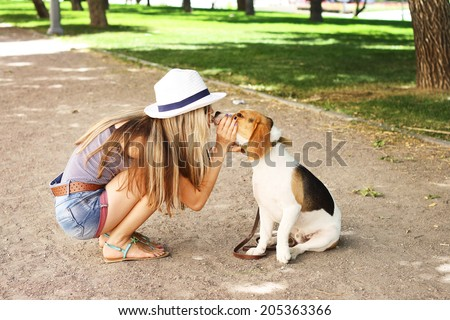 Cute girl kissing her beagle dog in nature outdoors. Lovely shot - stock photo