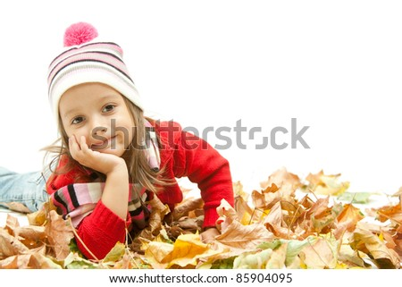 cute girl laying in colored autumn leaves - stock photo