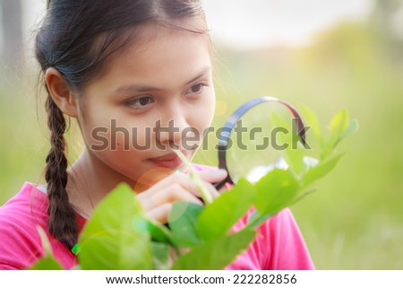 cute girl look for insect in garden - stock photo