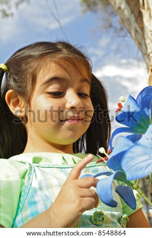 Cute Girl looking at Flowers - stock photo