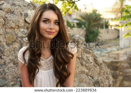 Cute girl looking at you. Young beautiful woman with curly hair outdoor portrait - stock photo