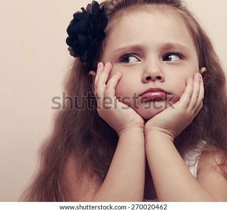 Cute girl looking sad with pouted lips and hands under face. Closeup portrait beautiful kid with long hair. Vintage - stock photo