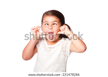 Cute girl making funny face sticking tongue out and crossed eyes, isolated. - stock photo