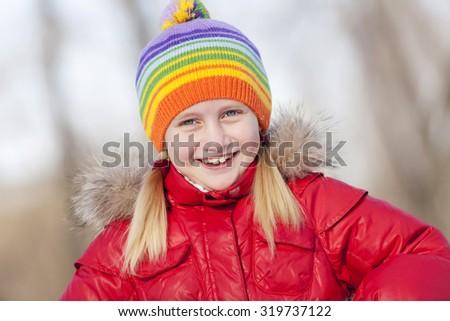 Cute girl of school age having fun in winter park - stock photo