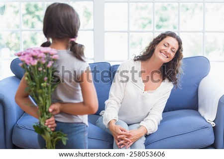 Cute girl offering flowers to her mother in the living room - stock photo