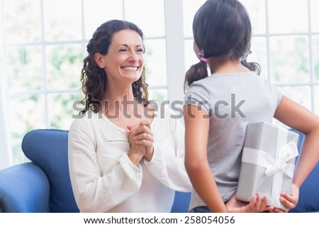 Cute girl offering gift to her mother in the living room - stock photo
