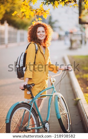 Cute girl on a vintage bike in the city - stock photo