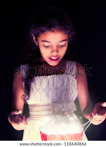 cute girl opens a present bag - stock photo