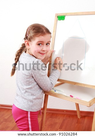 Cute girl painting on chalkboard - stock photo