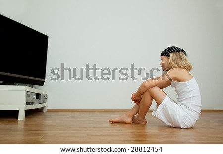 Cute girl passing freetime in childhood watching tv - stock photo