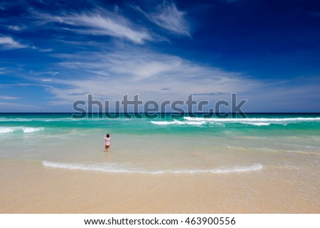 Cute girl play in the waves on sea.