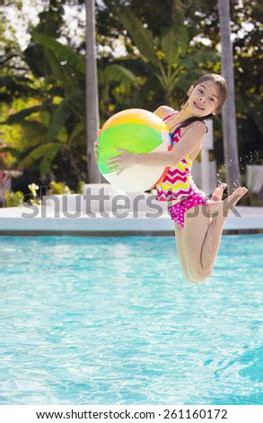 Cute Girl playing and jumping in the swimming pool - stock photo