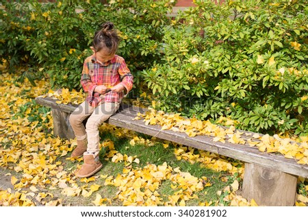 Cute girl playing in fallen leaves