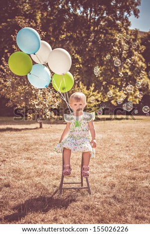 Cute girl playing in the park with soap bubbles and balloons