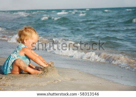 cute girl playing on beach - stock photo