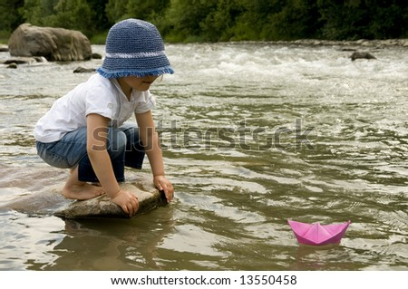 Cute girl playing with paper boats - stock photo