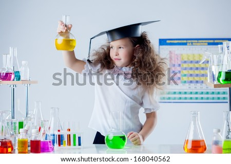 Cute girl posing with colorful test-tubes in lab - stock photo