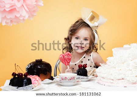 Cute girl posing with sweets, on yellow background - stock photo