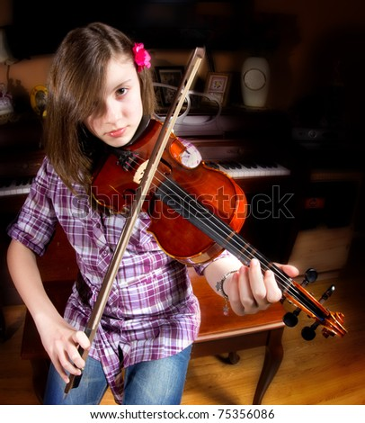 Cute girl practicing her violin - stock photo