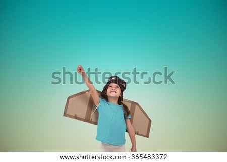 Cute girl pretending to be pilot against blue sky - stock photo