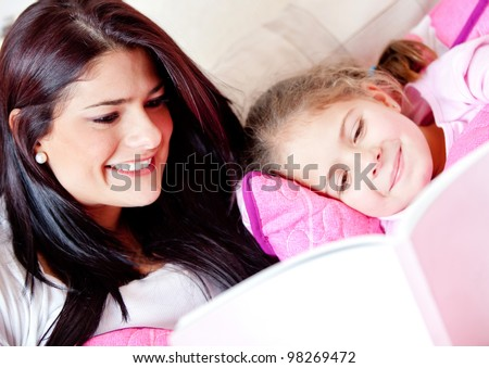 Cute girl reading a bedtime story with her mother - stock photo