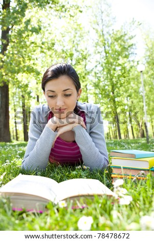 cute girl reading a book and lying on the grass outside - stock photo