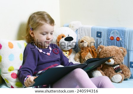 Cute girl reading a book on her bed with toys around her - stock photo