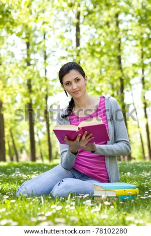 cute girl reading a book on the grass outside - stock photo