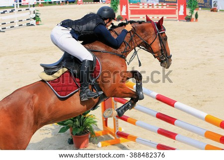 Cute girl riding jumps over a hurdle on horse races - stock photo