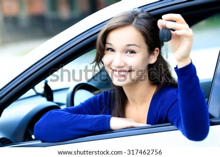 Cute girl shows a car key - stock photo