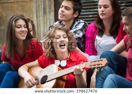 Cute girl singing with a group of friends on the street - stock photo