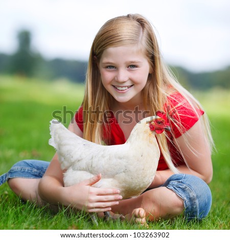 cute girl sitting in the grass with her white chicken - stock photo