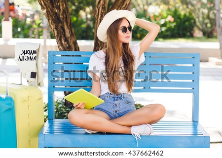 Cute girl sitting on a blue bench and playing on a tablet in yellow case. She wears denim shorts, white t-shirt, dark sunglasses, white sneakers and straw hat. She sits with two suitcases next to her. - stock photo