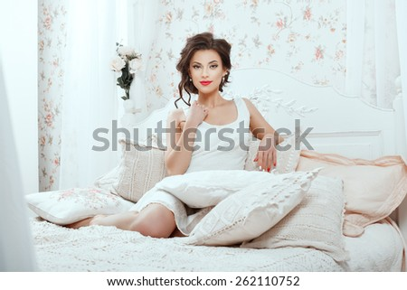 Cute girl sitting on a white bed among pillows.
