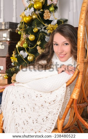 cute girl sitting on armchair in christmastime indoors