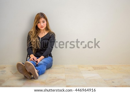 Cute girl sitting on the floor and holding a mobile phone