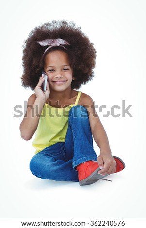 Cute girl sitting on the floor having a phone call on white screen