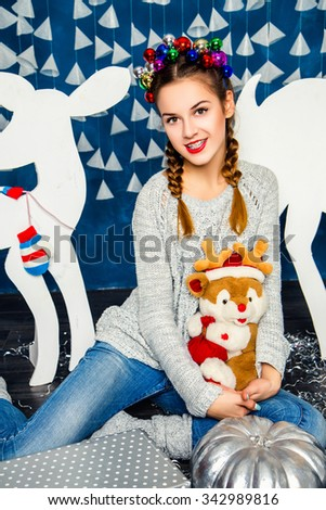 Cute girl sitting with a plush toy in the hands against the backdrop of a blue wall with white garlands. Christmas and New Year concept