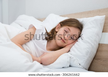 Cute Girl Sleeping With White Blanket In Bed - stock photo