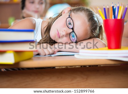Cute girl studying in classroom at school - stock photo
