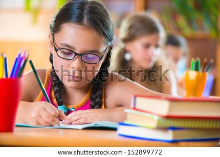 Cute girl studying in classroom at school