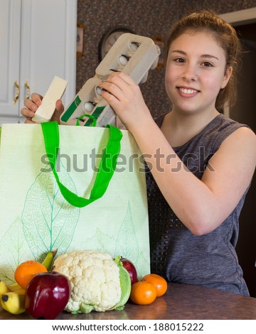 Cute girl unpacking healthy groceries from a reusable green bag